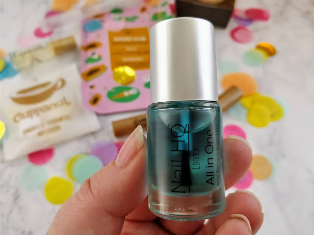 Hand holding bottle containing blue liquid, the Nail HQ All In One Oil