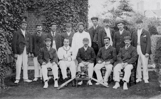 Photograph of North Mymms Estate Cricket Club 1902-06. Centrally seated figure is Charles Fielder, head gardener, to his left is Mr Finch Foreman, gardener, to his left is Mr Ernest Bristow, foreman of the rose garden. Note North Mymms House in the background. Image from G. Knott