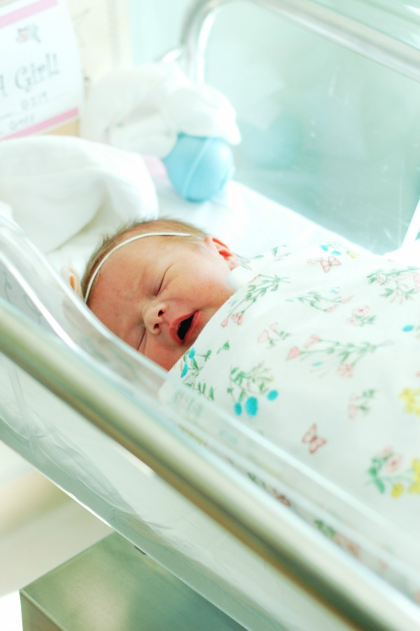 Baby wrapped in blanket from baby registry in hospital.