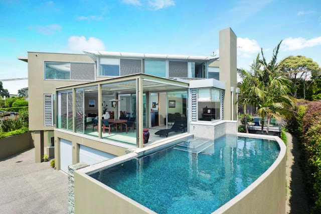 Photo of an amazing modern house as seen from the pool side