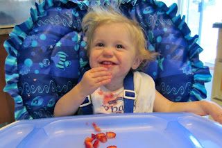 baby in high chair eating strawberries