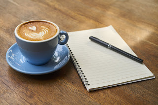 A notebook, pen and cup of coffee on a desk.