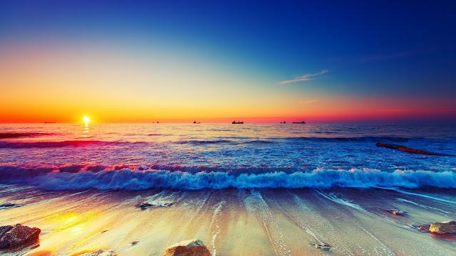 Mooie zonsondergang wallpaper met boten in de zee.