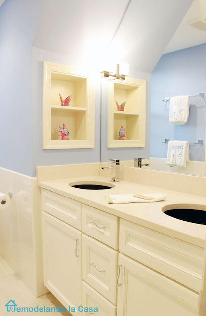 Small bathroom with double vanity and wall storage niche