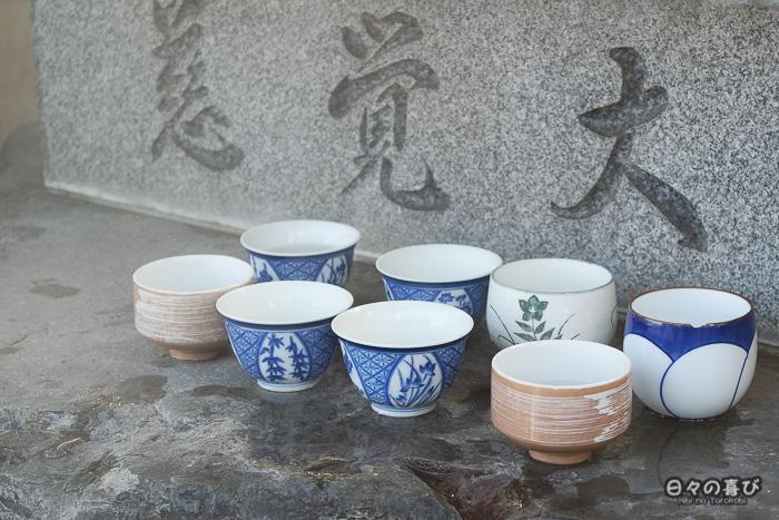 tasses alignées au pied d'une statue