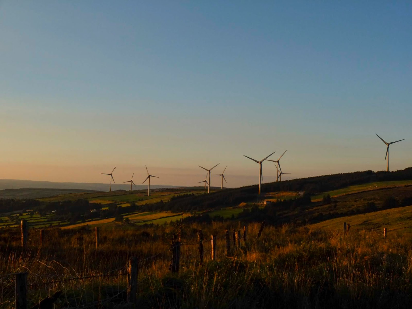 Windmills on a hillside in the Boggeragh Mountains during golden hour.