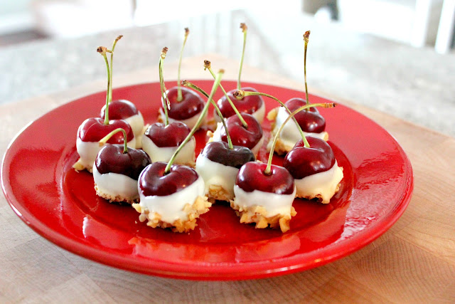 red plate filled with cherries dipped in white chocolate and dipped again in chopped nuts