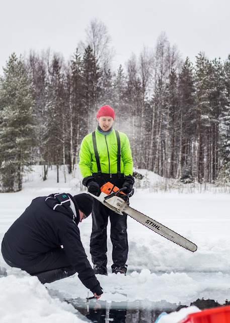 Mies seisoo jäällä avannon edessä pitkälapaisen moottorisahan kanssa ja toinen valokuvaa avantoon