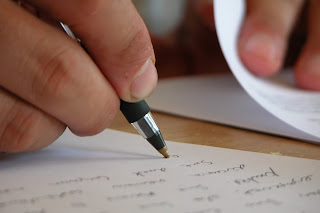 Photo of man's hand writing a statement.