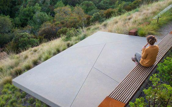 Amenajare gradina in panta, graminee, terasa beton, banca de lemn.