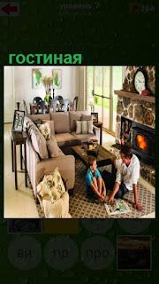 в гостиной с камином на полу отец с ребенком сидят