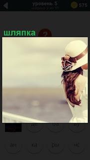 На фоне воды стоит девушка в белой шляпке и белом пальто с выпущенными волосами