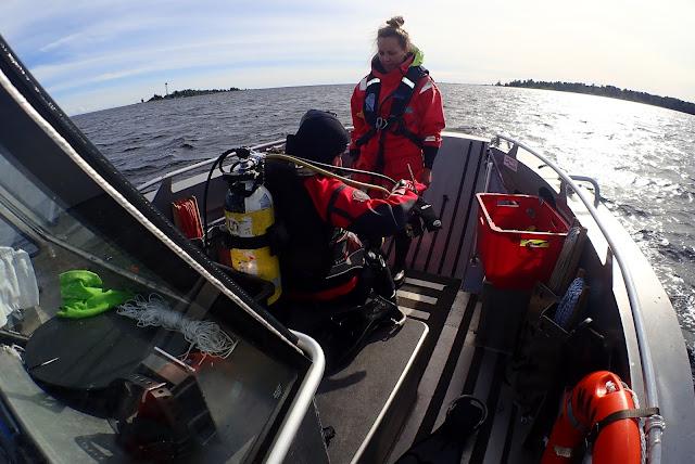 Kaksi työntekijää valmistautuu sukellukseen veneessä.