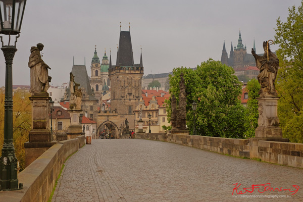 At dawn, looking back to the castle along the statue lined Charles Bridge in Spring Prague by Travel and Lifestyle Photographer Kent Johnson.