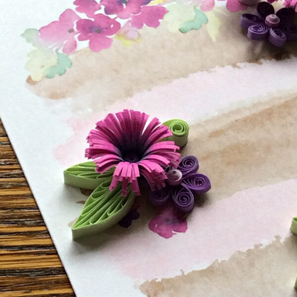 quilled flowers and leaves in pink, purple and green on a watercolor painting