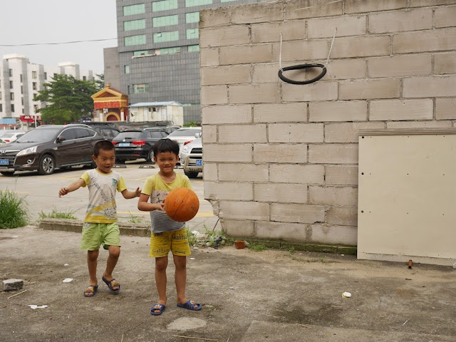 boys playing basketball with a hoop made out of a bicycle tire in Zhuhai, China