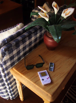 Modern dolls' house miniature sofa table and sofa. On the table is a pot of lilies, a pair of sunglasses, a Gameboy and a Nokia mobile phone.