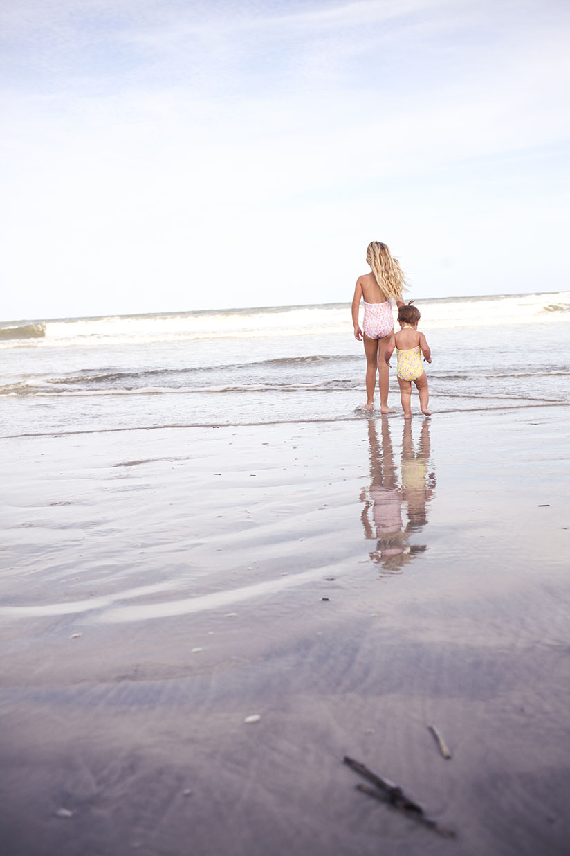 Sisters walk in the water on the beach