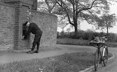 Photograph of a postman collecting mail from the wall box at the corner of Osborne Road and Hawkshead Road, Little Heath in 1960. Image from Ron Kingdon, part of the Images of North Mymms collection