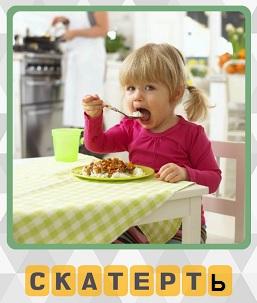 ребенок за столом ест кашу который накрыт скатертью