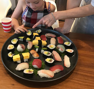 A round platter of both nigiri and nori rolls with hand pointing at them