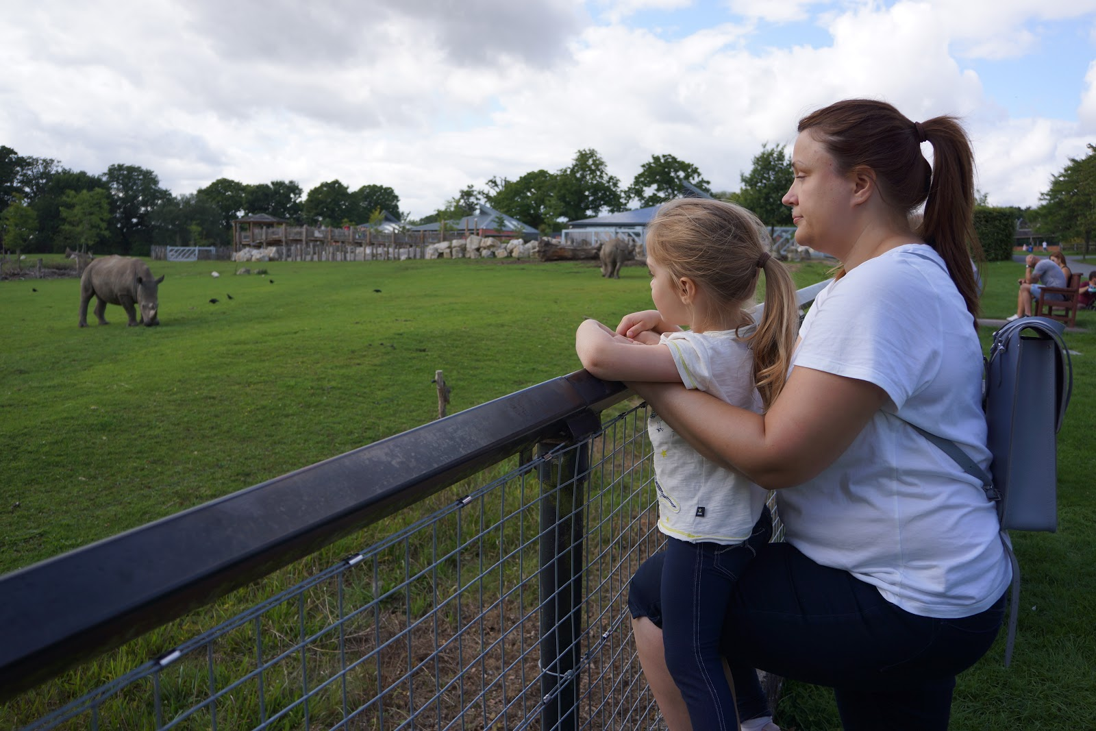 mum an daughter watching rhinos at a zoo