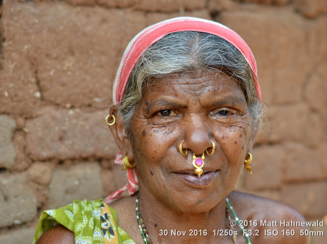 tribal; Adivasi; Christian; Matt Hahnewald Photography; Facing the World; photography; photo; image; face perception; physiognomy; psychological; educational; lively; outstanding; favourite; superior; interesting; Nikon D3100; Nikkor AF-S 50mm f/1.8G; prime lens; 50mm lens; 4 : 3 aspect ratio; horizontal format; street; portraiture; portrait; closeup; headshot; seven-eighths view; brown; outdoor; colour; cultural; character; personality; real people; human head; human face; human eyes; nose; facial expression; eye contact; consent; empathy; rapport; respect; encounter; relationship; emotion; ethnic portrait; Kuvi Kondh tribe; Upper Bombu; Orissa; East India; one person; female; adult; posing; smiling; soulful; earrings; nose jewellery; old woman; headscarf; smiling eyes; villager; nose ring; tradition