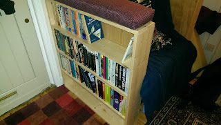 A chair with book storage in the arms and big cushions