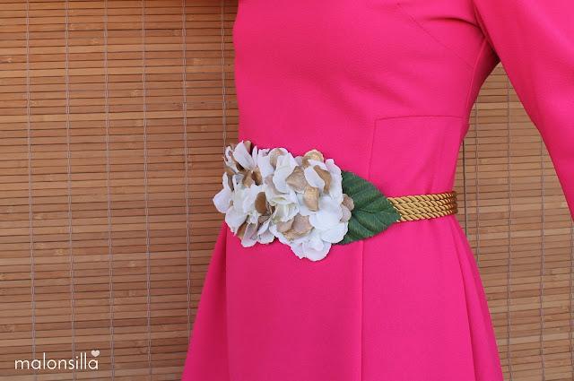 Cinturón de flores para boda en blanco y dorado con hojas verdes de cordones dorados.