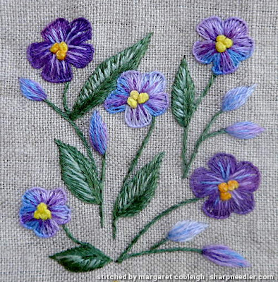 Detail of central purple floral motif on Herbier. Flowers and leaves are stitched with House of Embroidery variegated threads.