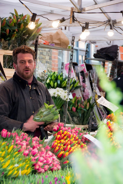 A market stall owner selling tulips