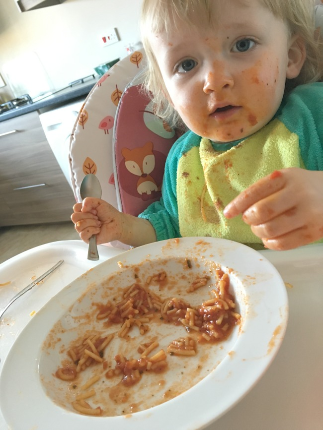 toddler with red face and bowl of spagetti