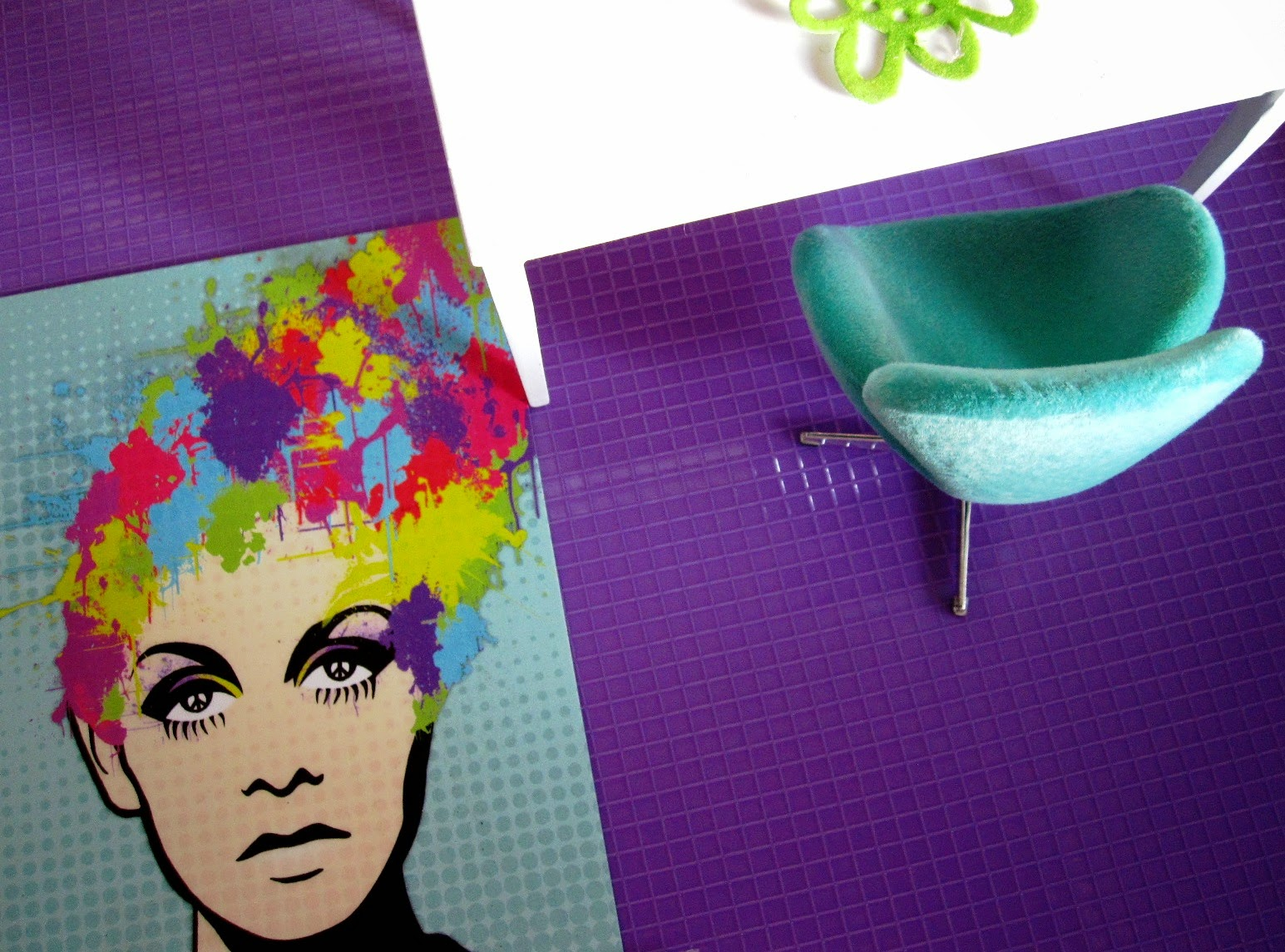 Modern dolls house white table, swan chair, colourful postcard and purple tiled floor:view from above.