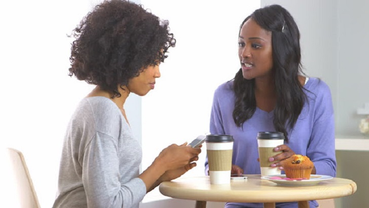 Black couple talking while having a coffee