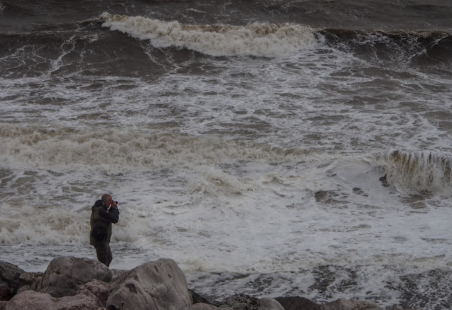 Photo of Phil getting a closer view of the waves on the shore at Maryport