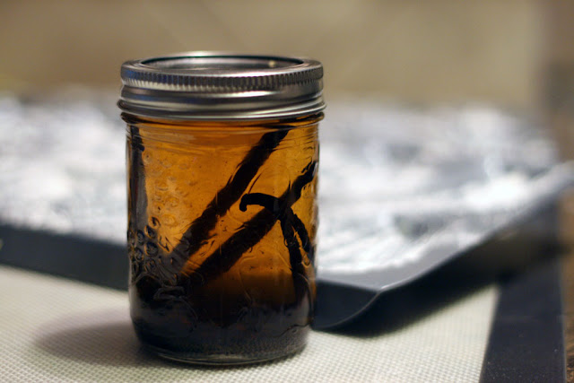 Pieces of vanilla bean in a jar filled with vodka. The vodka is tinted brown from the vanilla bean and seeds.