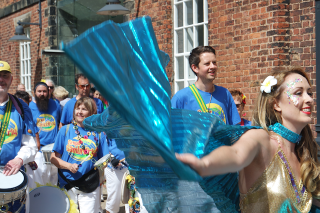 a female dancer wearing a blue cape and face glitter leading a group of drummers