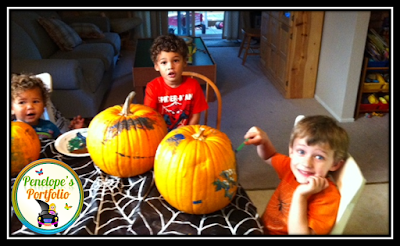 Three children seated a table with a spiderweb tablecloth, and painting pumpkins with paint