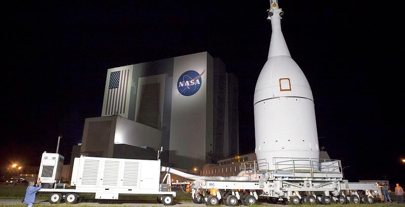 At NASA's Kennedy Space Center in Florida, the agency's Orion spacecraft pauses in front of the spaceport's iconic Vehicle Assembly Building as it is transported to Launch Complex 37 at Cape Canaveral Air Force Station. Credit: NASA/Frankie Martin