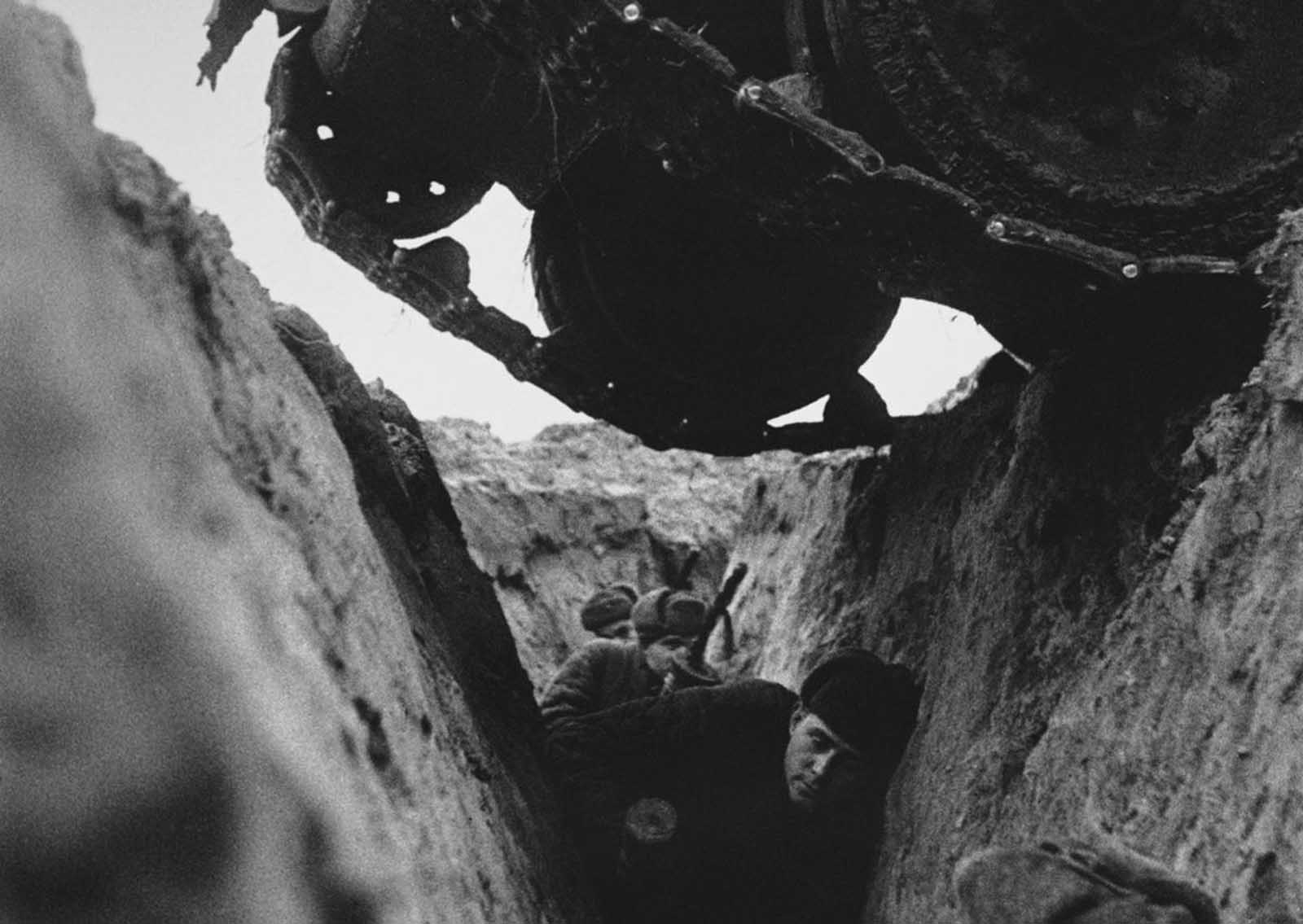Red Army soldiers in a trench as a Russian T-34 tank passes over them in 1943, during the Battle of Kursk.