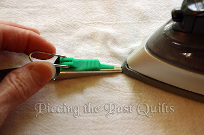 Guide the bias tape maker, keeping the fabric feeding straight, as you push the iron.