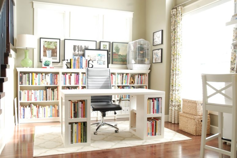 feminine corporate office blue carpet flooring dark varnished wall mounted bookshelf white gloss plywood workspace table wooden writing desk grey fabric working chair with four wheels