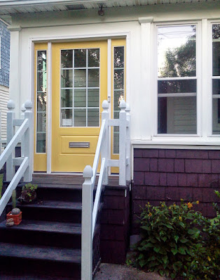 The front stoop with yellow door and white railings
