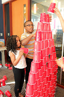 Two kids build a tower with red cups