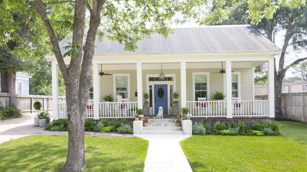 Charming cottage exterior with rocking chairs on the front porch, a right blue door, and a sweet do. Design by Holly Mathis. #cottage #exterior #frontporch #hollymathis