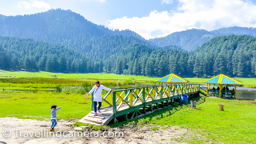 Lush green meadows, grazing sheeps, beautiful cottages, high deodars and high hills of Khajjiar makes it a popular destination for traveller, explorers and tourists from India & abroad. Khajjiar is also known as mini Switzerland of India. Khajjiar is located on the way from Dalhousie and Chamba. This Photo Journey shares more about the ways to reach Khajjiar and other interesting things to explore & do around Khajiar/Dalhousie.How to reach?Here I am sharing details about reaching Khajjiar from Delhi and then will share some pointers about options from Chandigarh, Amritsar, Jalandhar etc. HRTC bus for Chamba starts from Delhi at 7pm. The link shares has more details about booking bus from Delhi to Dalhousie. The one which starts at 7pm is 2*2 AC bus. Apart from this 2 ordinary buses go from Delhi to Chamba/Dalhousie. Any of these buses can drop you at Dalhousie, which is closest main station near Khajjiar. Khajjir is just 22 kilometers from Dalhousie.   Other option to reach Khajjiar is by taking a train from Delhi to Pathankot. From Pathankot, you can either hire a taxi or board local bus from Dalhousie. Please note that most of the buses going to Chamba can drop you at Dalhousie but there is rare possibility to find direct bus for Khajjiar. There are few buses from Dalhousie to Chamba which cross through Khajjiar. There is one which starts from Dalhousie at 9:15am. When I was staying in Dalhousie, I chose to take this bus to reach Khajjiar and then took 2:30pm bus to come back. Expect lot of passengers in these buses between Dalhousie and Khajjiar.   If you are coming from other cities like Chandigarh, Amritsar, Jalandhar, Dharmshala or Shimla; there are various bus routes. Check HRTC, PRTC websites to know timings. Apart from these private buses are also available for Dalhousie. Hope these details are helpful. If not, please drop a comment with your specific question and I will try to share appropriate details. Let's talk about options to stay around Khajjiar. Where to stay? I have been to Khajjiar many times, but most of the times stayed in Dalhousie. I wish to spend a night around Khajjiar. There is one HPTDC hotel which faces Khajjiar lake (dry lake). Apart from this there is one forest guest house and a HPPWD guest house around Khajjiar. All of these beautiful properties are best located around lush green meadows of Khajjiar. Apart from these prime location properties, there are few resorts around Khajjiar, but they are not around the main lake. 3 options mentioned above offer brilliant views of lush green grounds of Khajjiar. During summers, it's hard to get booking in Khajjiar. The next good option is Dalhousie. Dalhousie has comparatively more hotels & resorts. But it's recommended to do advance booking if you are going to Khajjiar or Dalhousie in main tourist season. Activities at Khajjiar -   1. Paragliding - Now you can enjoy paragliding at Khajjiar. Like Solang nala, kids can also enjoy small flights within Khajjiar and adults can enjoy the longer flights from surrounding hills, which usually land in Khajjiar. 2. Horse riding - You can ride around the Khajjiar. There is a proper path defined for horses and this is one of the early & popular activity to enjoy at Khajjiar. The horse owners also tell you few tricks to ride the horse. On the halfway, you feel like controlling the horse on your own :). That's fun ! 3. Zorbing - You would see zorbing balls rolling on other side of Khajjiar lake. 4. Photo shoot in Himachali dress - This is typical activity which is offered in most of the hill stations in Himachal and Kashmir. I think, I need not explain this more. 5. Interacting with rabbits and getting some photographs clicked - You would find few kids with rabbits. They allow you clicking photographs with these rabbits and charge 10 rs. During tourist season, they may ask 20 rs or so. 6. Enjoy local folk music - There is a gentleman, who sings local songs around the dry lake of Khajjiar. He sings brilliantly and you can find his videos on Youtube.You can carry your own stuff with you. Many times, we carry Badminton, frisbee, a football and picnic stuff. Khajjiar is appropriate place for picnic. Folks living in Dalhousie and Chamaba usually come to Khajjiar during sundays with friends and family.Main places to  explore around Khajjiar - Dalhousie - Churches, Mall road, walks Panchpula Waterfalls Dainkund TrekKalatop wildlife sanctuary trek, Chamera Lake Dam, Chamba Town - Bhuri Singh Museum, Laxmi Narayan Temple, Chattradi Temple, Chugan and lot more , Ravi river , View of snow covered Pir Panjal mountain ranges, I was there in Khajjiar again in August and it looks awesome in the month of August & September. It was a day out with my niece Urvi and enjoyed clicking her photographs. Above photograph shows deodar cones. August is the month when you can see all these cones on deodar trees. Khajjiar is surrounded by dense forest of high deodars. There is water in the middle of the lake. More than water, it's quicksand. This wooden pathway takes you to the water pond and this time I saw lot of fish in this. Although scene is not very interesting. Kids really enjoy to see fish in the pond. A gentleman sits around this place and sell some eatable for the fish. That's a good way for kids to interact with fish. Direct sunlight, fresh & cold breeze, lush green meadows, grazing sheep & cows, beautiful huts surrounded by dense forests of Deodar make Khajjiar a irrisistable place in Himachal Pradesh . Khajjiar is my favorite place around Dalhousie and Chamba regions of the himalayan state. Here is a panorama of Khajjiar. Notice the size of people walking around and try to imagine the size of this beautiful green meadow. It's huge. If you love walking, this is perfect place with appropriate weather. At times sun can be too harsh, so choose to walk around the edges with shade of deodars. Hope this post would help you plan your trip to Khajjiar and by now you must have an idea about things to expect at Khajjiar. Please feel free to drop your comments for further questions or suggestions.