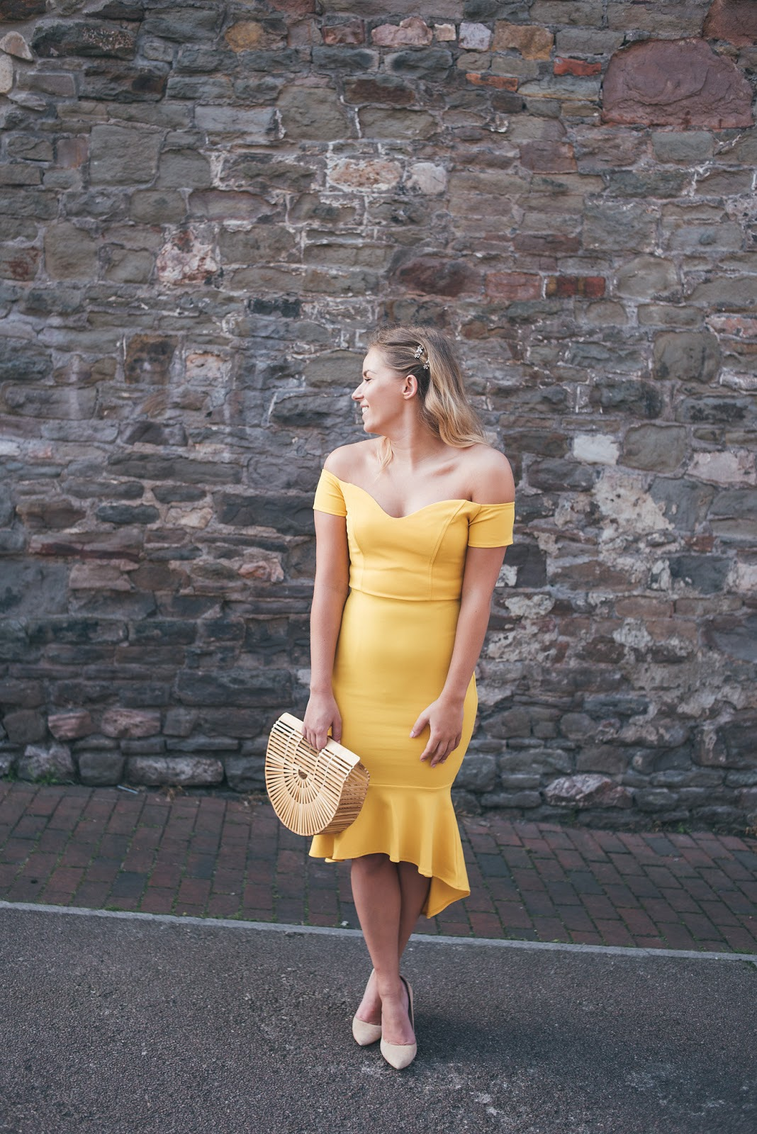 Rachel Emily in Yellow John Zack Dress from ASOS in Front of Stone Wall