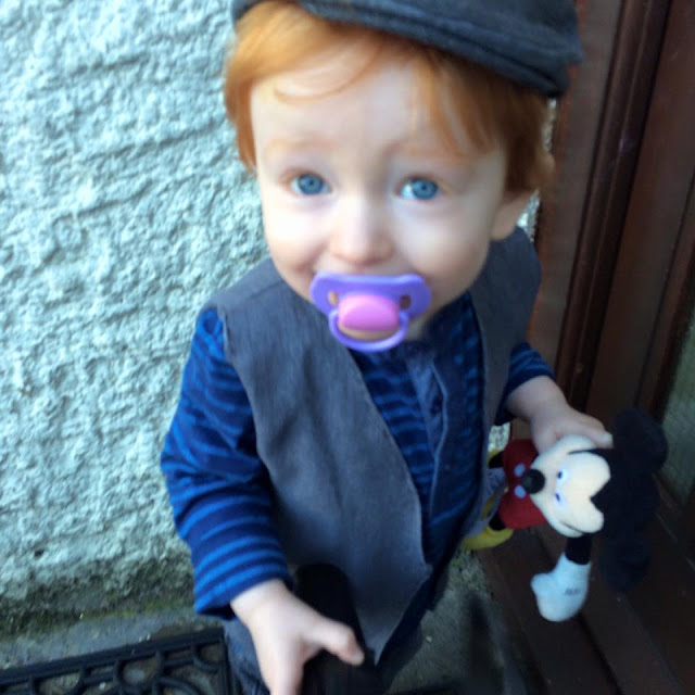 A red haired little boy dressed as a sweep