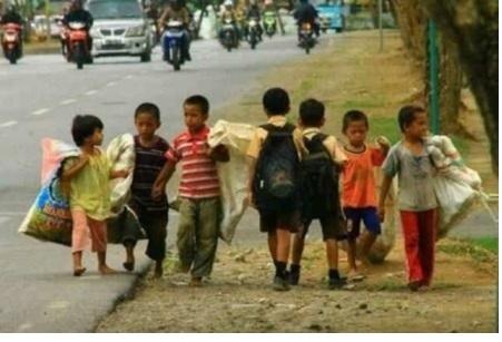 Anak-anak pemulung berjalan disamping jalan raya sambil membawa karung, dan antaranya di lewati 2 anak sekolah berbaju pramuka   Anak – anak mengunakan berbagai macam atribut dalam memprotes pendidikan