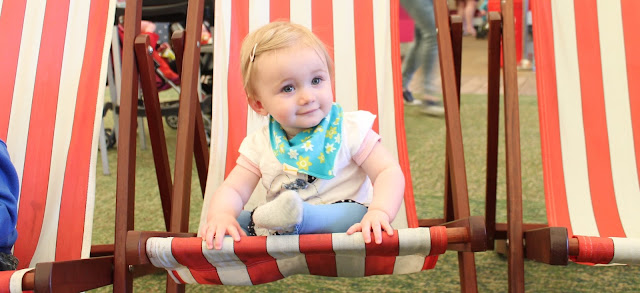 baby girl sat on red and white stripe deck chair at Butlins wearing colourful blue spring bib from funky giraffe